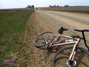 Bicycle laying on a gravel road in a rural setting