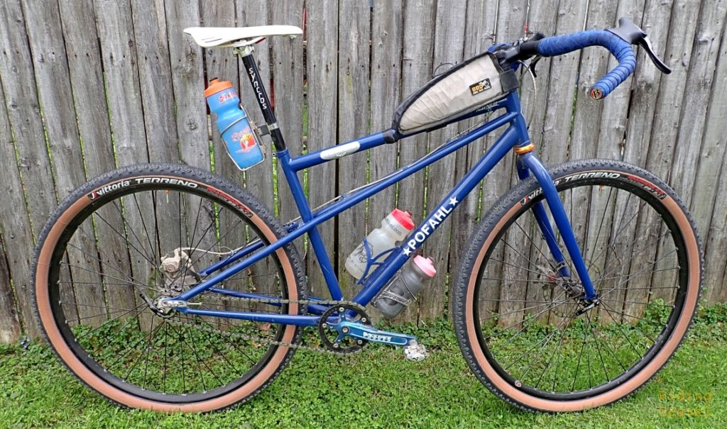 Blue bicycle against a fence