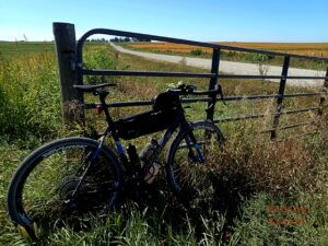 A bicycle leaning against a gate in a rural setting