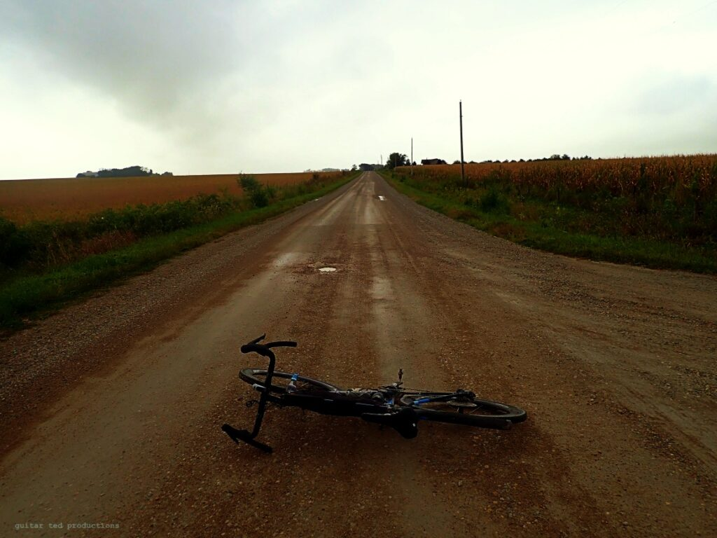 A bicycle laying on a rural road