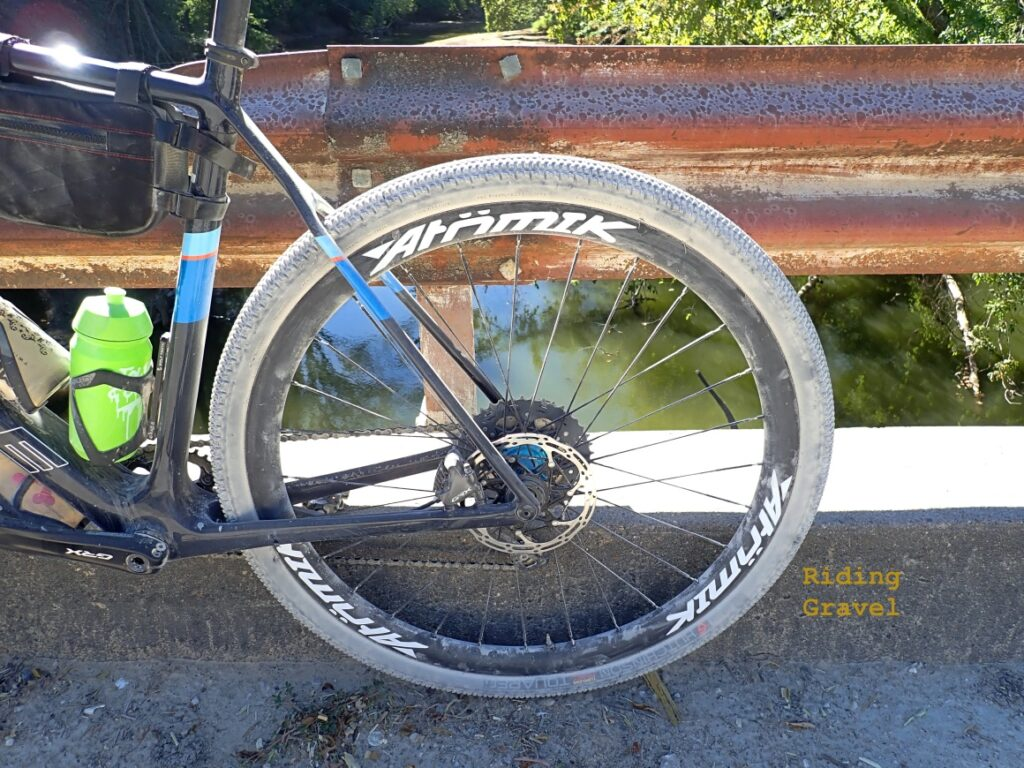 The Atomik/Berd Ultimate rear wheel on a bike against a railing