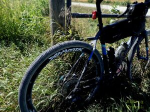 Bicycle leaning against a gate in a rural area.