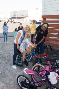 A child on a bike being assisted by adults.