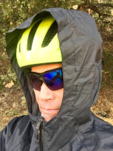 Detail shot of the Bontrager Avert Rain Jacket hood over a helmet
