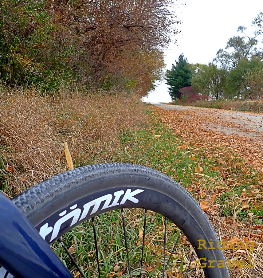 A rural road with a detail shot of an Atomik/Berd Ultimate wheel.