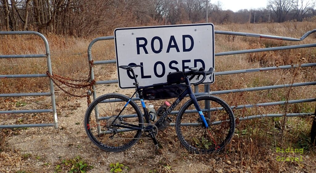 "A Bicycle leaning against a gate with a ""Road Closed"" sign sporting the WTB Byway SG2 gravel tires."