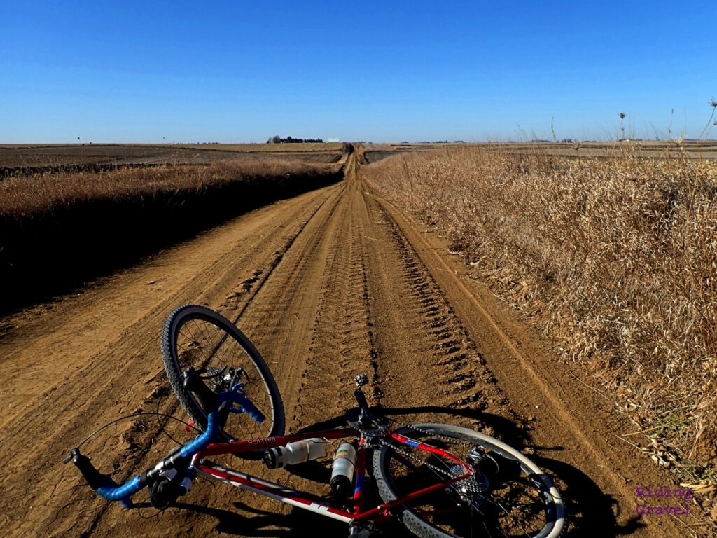 A bicycle laying on a dirt road.