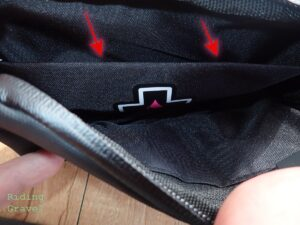 Red arrows pointing to the inner divider of the Muc-off Rainproof Essentials Case