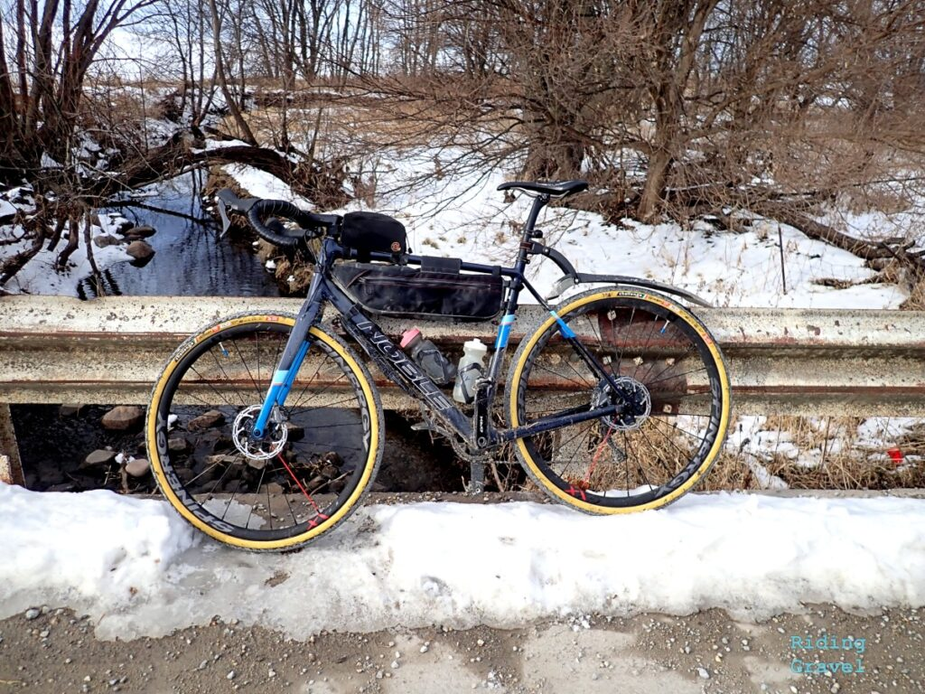 A bicycle leaning against a guard rail in a snowy scene.