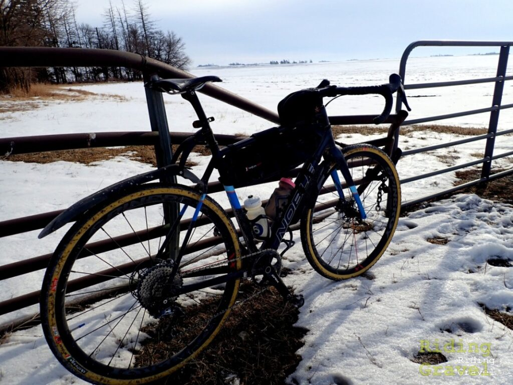 A bicycle leaning against a gate in a snowy setting