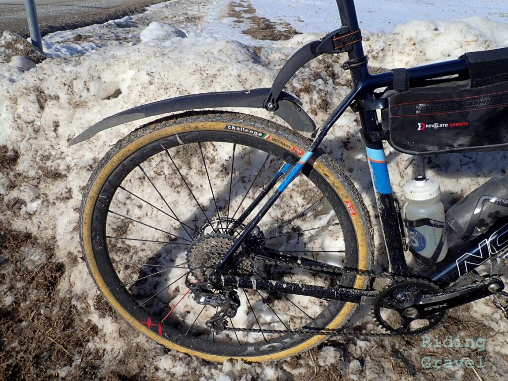 View of a rear wheel on a bicycle in a snowy situation.