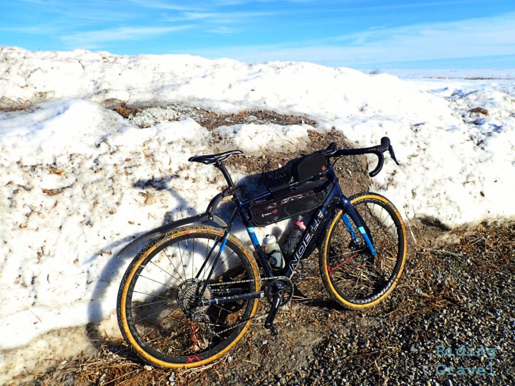 Bicycle leaning against a snow covered glacial erratic.