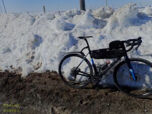 A drop bar bike leaned up against a snow bank.