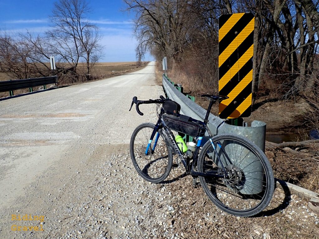 A bicycle leaning on a guard rail in a rural scene