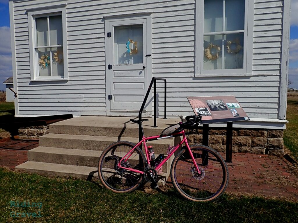 A pink bicycle leaning against a one room schoolhouse.