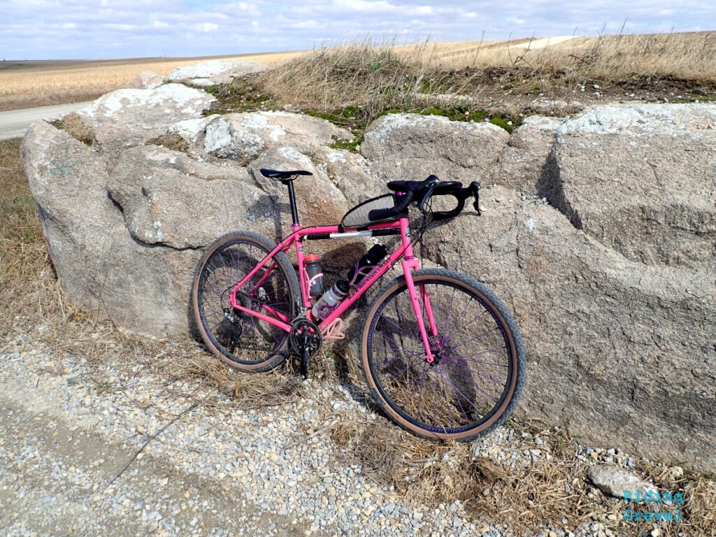 A pink bicycle leaning against a large glacial erratic
