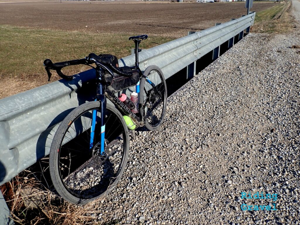 A bicycle leaning against a guard rail in a rural setting.