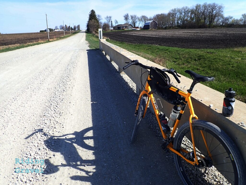 A yellow bike leaning against a bridge railing on a crushed rock road.