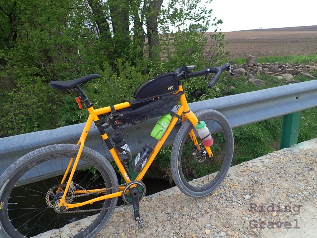 The Twin Six Standard Rando v2 with Panaracer Gravel King SK+ 650b tires leaning against a bridge rail in a rural landscape.