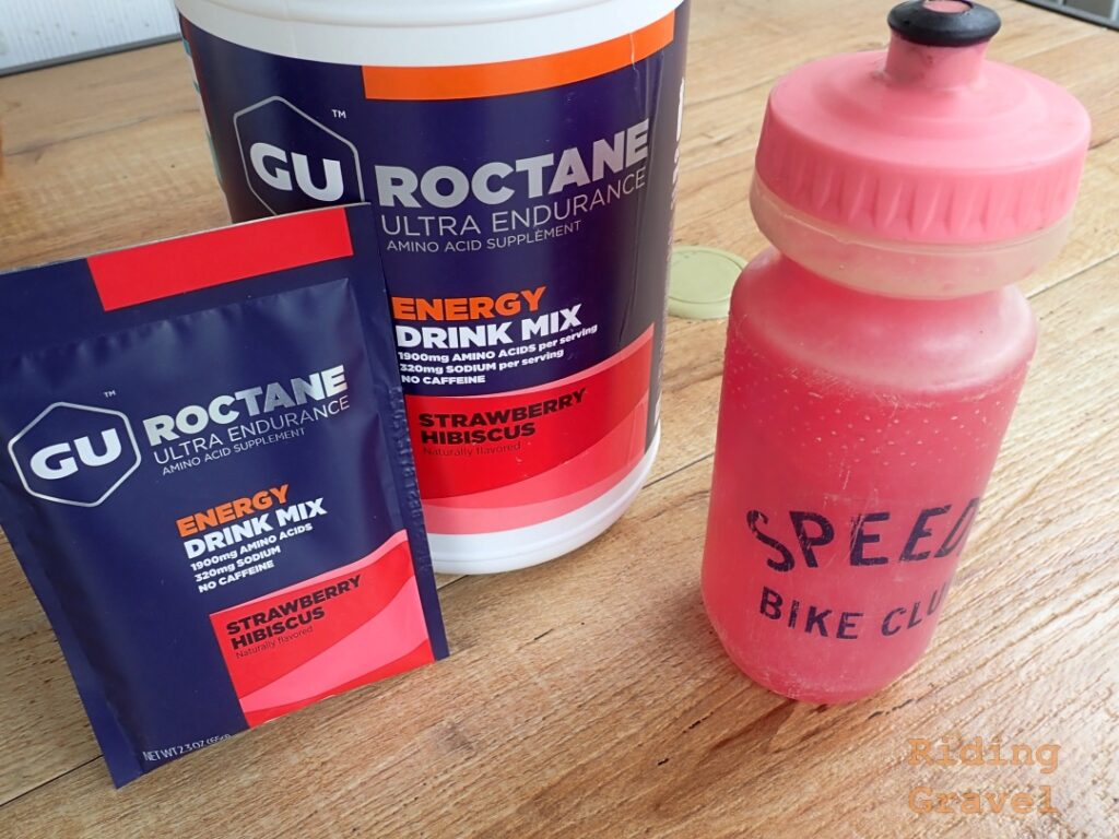 View of Gu Energy Roctane Strawberry Hibiscus flavored drink mix packages and a water bottle.
