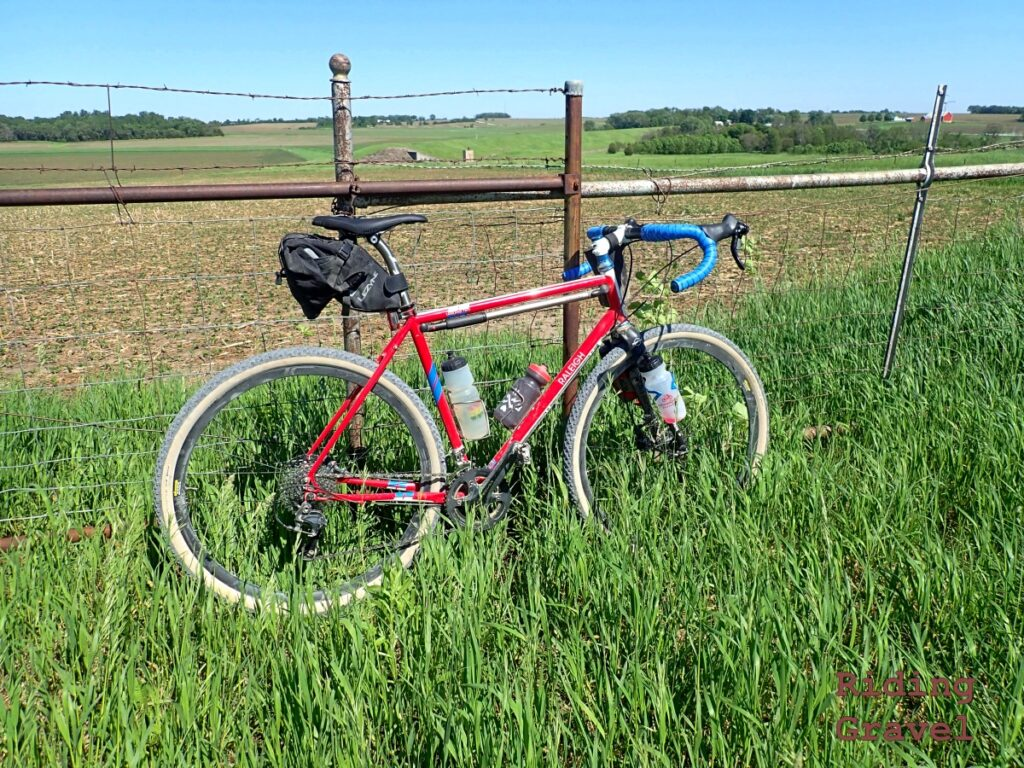 A bicycle leaning against a fence in a rural setting