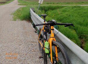 Scene of a bike leaning against a bridge rail in a rural setting