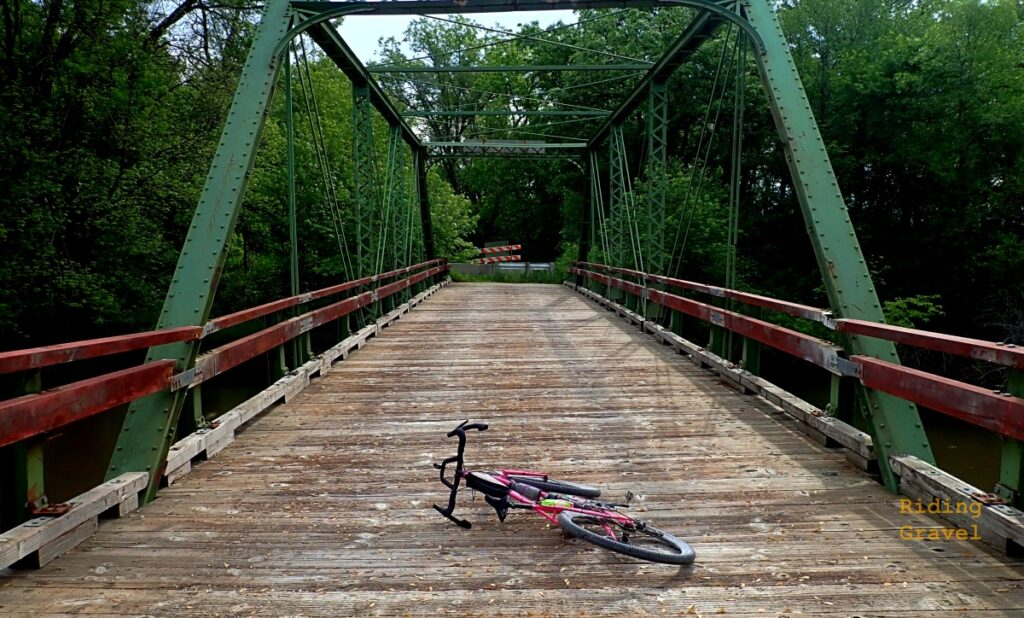 Scene of a bike laying on the deck of an old steel gabled bridge in a rural setting.