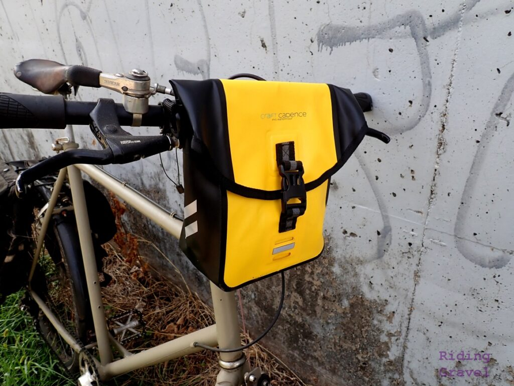 The Craft Cadence bag on a bicycle near a cement retaining wall.