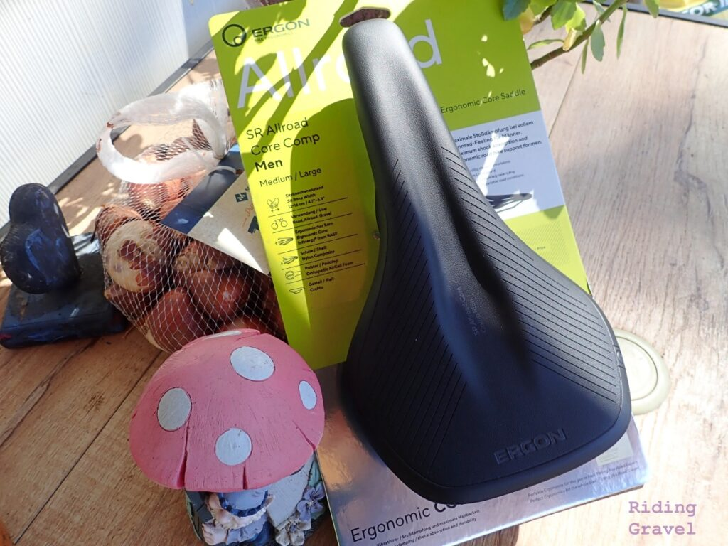 The SR Allroad Core Comp saddle on its retail hang tag sitting on a table in the Sun with other objects