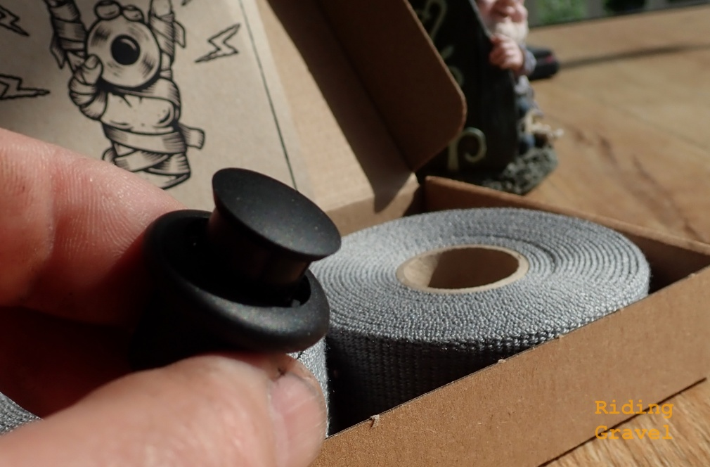A close up of the Grepp handle bar end plug with a roll of Grepp tape in the background.