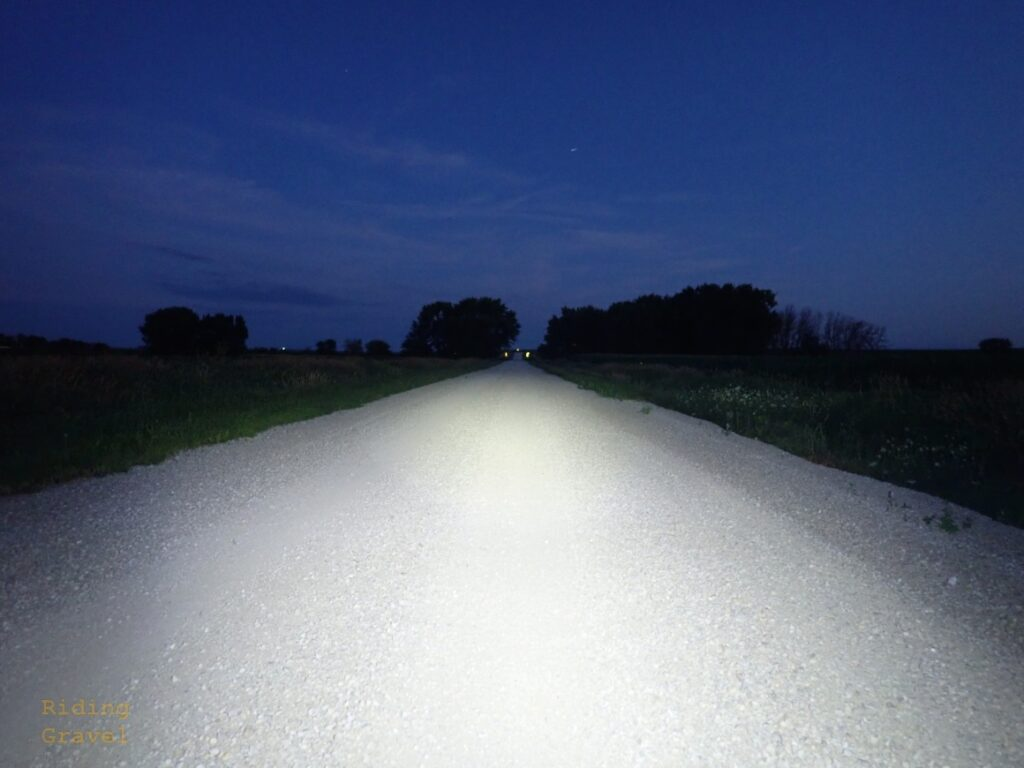 A rural gravel road lit up by an LED cycling light.